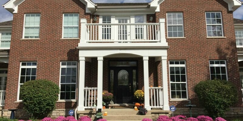 Brick home with white trims. Fall pink mums front yard