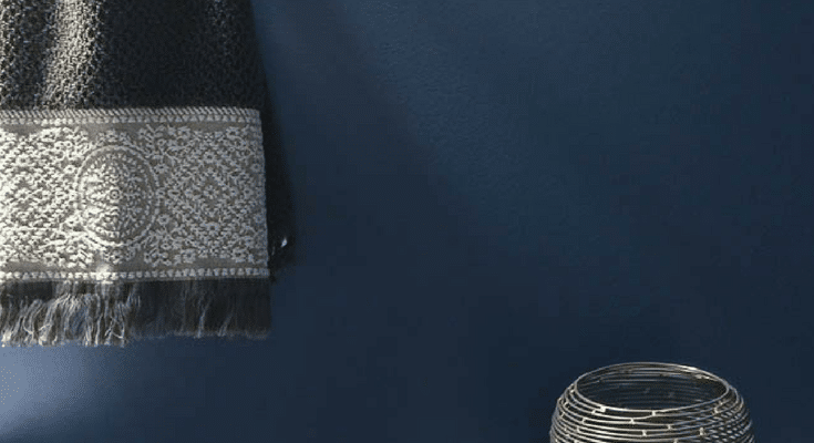 Image of Indigo Batik Navy Blue wall with gray towel and white toilet with a candle holder.