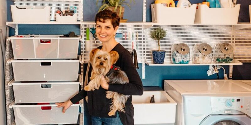 woman holding a Yorkshire terrier in blue laundry room