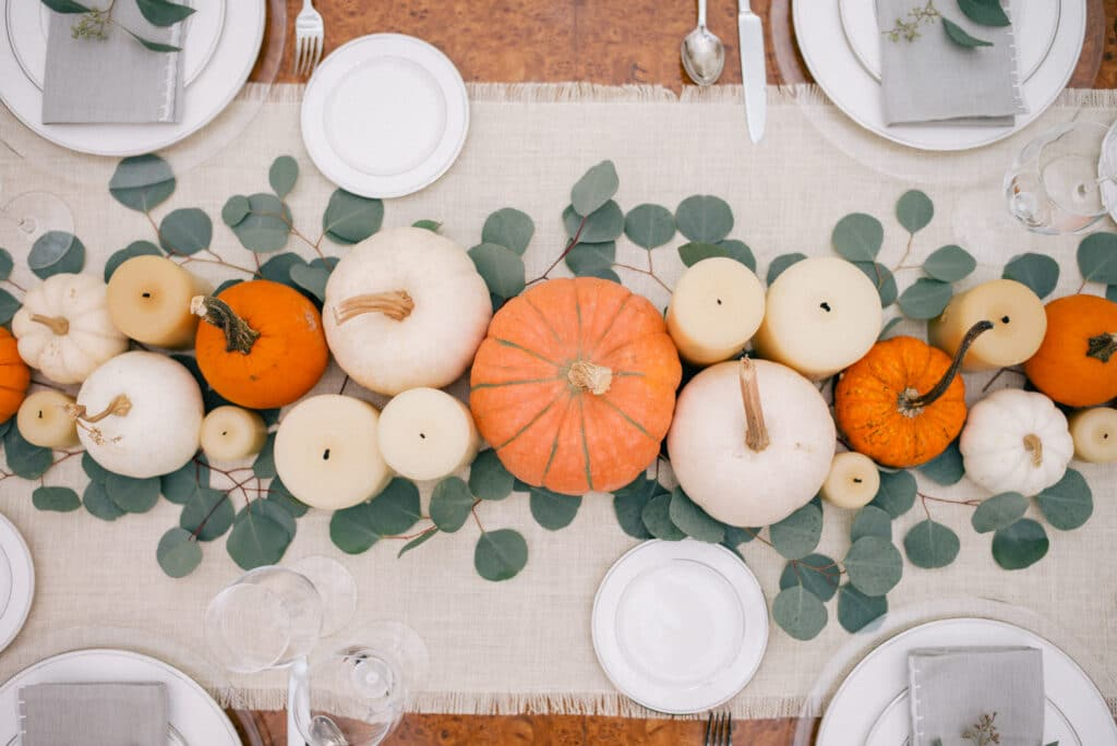 pumpkins, candles, and greenery on a Thanksgiving table